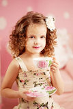 Little cute girl in a pink dress drinks tea with sweets in the c Stock Photo