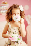 Little cute girl in a pink dress drinks tea with sweets in the c Stock Images
