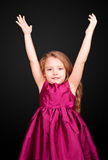 Little cute girl in a pink dress fun hands up Royalty Free Stock Images