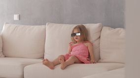 A little girl in a pink dress sitting on the couch attentively and emotionally watching TV in 3D glasses stock video footage