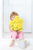 Little cute girl in pink dress sitting on white rustic porch and hides her face behind bouquet of yellow garden flowers. Stock Photography