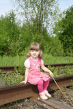 Little cute girl in pink dress with stick sits on old railway at Stock Photography