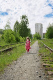 Little cute girl in pink dress walks at railway Stock Image