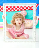Little cute girl in a pink suit sitting on the floor and smiling over wooden white frame. Royalty Free Stock Images