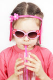 Little cute girl with pink sunglasses drinking water with a pipe Stock Images