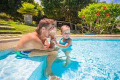 Little cute girl play with dad at the pool in Royalty Free Stock Photo