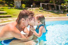 Little cute girl play with father at the pool in Royalty Free Stock Photography