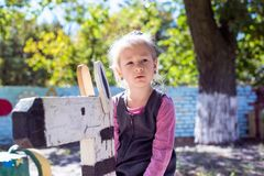 Little cute girl on the playground in the summer stock images