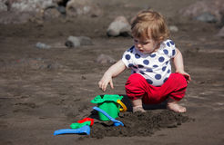 Little cute girl playing in the black volcanic sand. Little girl aged 2 playing on the beach with pail and shovel, Canary Islands royalty free stock image