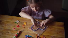 Little cute girl playing with colorful mosaic. stock video footage