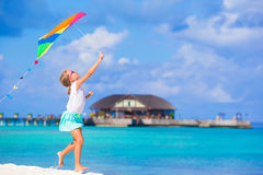 Little cute girl playing with flying kite on Royalty Free Stock Images