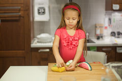 Little cute girl playing in the kitchen with Royalty Free Stock Photos