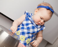 Little cute girl playing in kitchen Royalty Free Stock Images