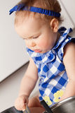 Little cute girl playing in kitchen Stock Images