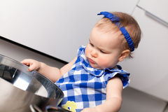 Little cute girl playing in kitchen Stock Photos