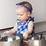 Little cute girl playing in kitchen Stock Image