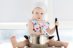 Little cute girl playing in kitchen with pots stock image
