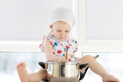Little cute girl playing in kitchen with pots stock photography