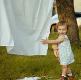 Little cute girl playing with laundry outside on Royalty Free Stock Photo