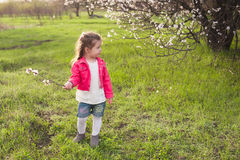 Little cute girl playing in the lush garden Royalty Free Stock Images