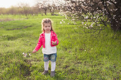 Little cute girl playing in the lush garden Royalty Free Stock Photo