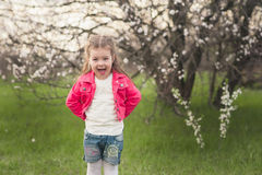 Little cute girl playing in the lush garden Royalty Free Stock Image