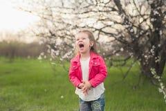 Little cute girl playing in the lush garden Stock Photos