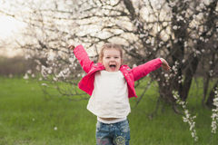 Little cute girl playing in the lush garden Stock Images