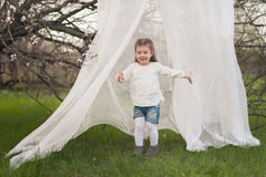Little cute girl playing in the lush garden Royalty Free Stock Photos