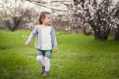 Little cute girl playing in the lush garden Royalty Free Stock Photography