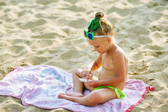 Little cute girl playing with phone at beach Royalty Free Stock Photo