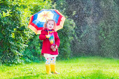 Little cute girl playing in the rain Royalty Free Stock Photos