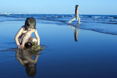 Little cute girl playing in sand on shore Royalty Free Stock Photos
