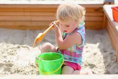 Little cute girl playing in sandbox Stock Photo