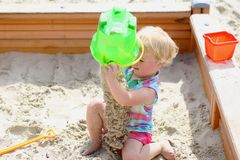 Little cute girl playing in sandbox Stock Photos