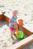 Little cute girl playing in sandbox Stock Photos