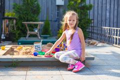 Little cute girl playing at the sandbox with toys Stock Photo