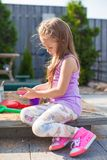 Little cute girl playing at the sandbox with toys Stock Image