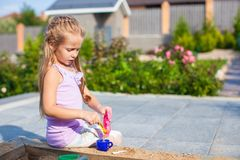 Little cute girl playing at the sandbox with toys. In the yard Royalty Free Stock Photo