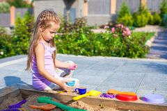 Little cute girl playing at the sandbox with toys Royalty Free Stock Images