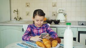 Little beautiful girl playing smartphone at morning while sitting at table in kitchen. Childhood, people, and technology. Little cute girl playing smartphone at stock footage
