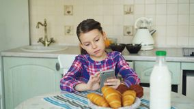 Little beautiful girl playing smartphone at morning while sitting at table in kitchen. Childhood, people, and technology. Little cute girl playing smartphone at stock video