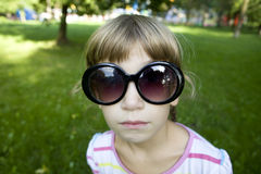 Little cute girl playing spy in park Royalty Free Stock Photo