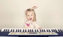 Little cute girl  playing on synthesizer Royalty Free Stock Image