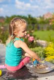 Little cute girl playing with toys in the yard Stock Images