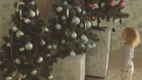Little cute girl points with finger Christmas balls on decorated tree. Little blonde baby girl points with finger on blue Christmas balls on one of the decorated stock video footage