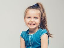 Little cute girl portrait close-up in jeans dress Royalty Free Stock Images
