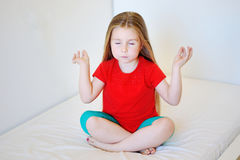 Little cute girl practicing yoga pose. At home Stock Image