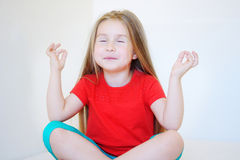 Little cute girl practicing yoga pose. At home Stock Photo