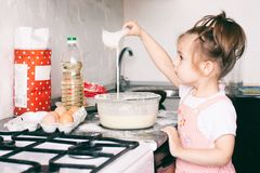 A little cute girl preparing the dough in the kitchen at home stock photos